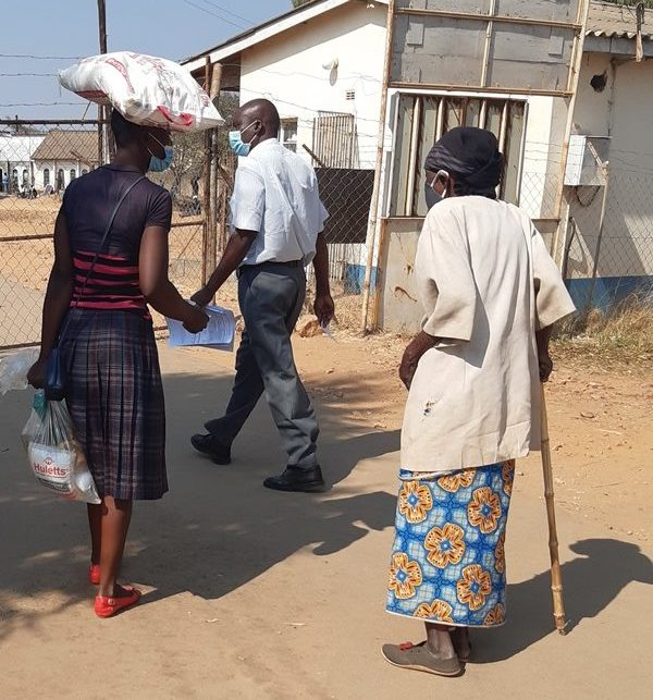 A photo of an older woman patient who is accompanied by a relative and who received a food hamper.