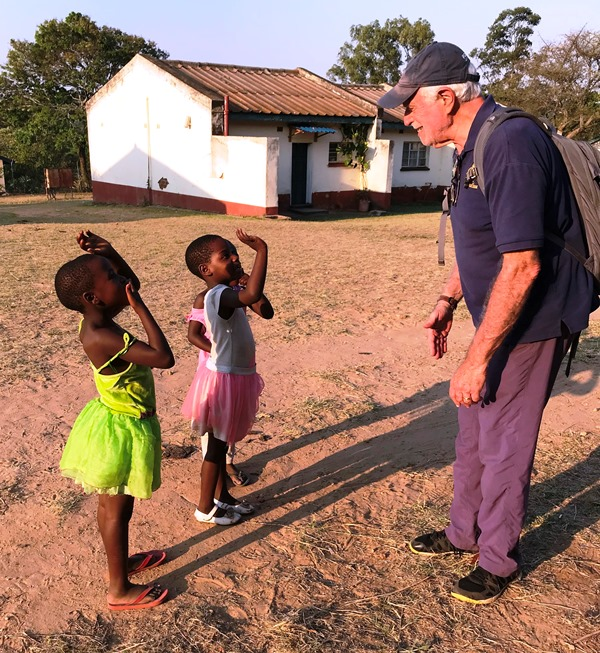 Photo of Dr. Lowell Schnipper talking with children along the hospital path during the 2019 visit to St. Albert's Mission Hospital.